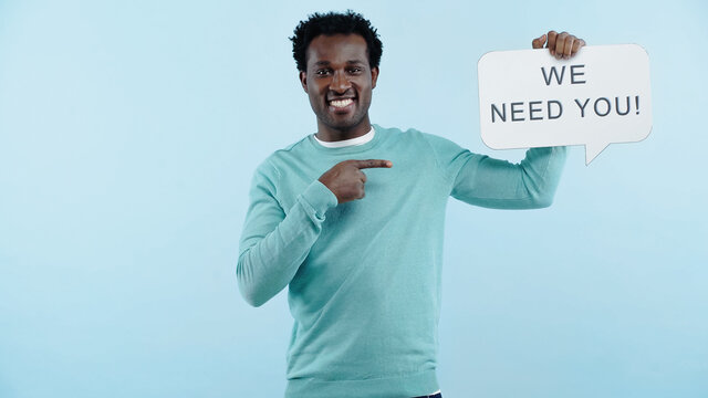 pleased african american man pointing with finger at speech bubble with we need you lettering isolated on blue