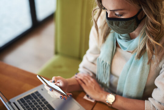 Young adult freelance woman doing her work at a coffee shop during pandemic