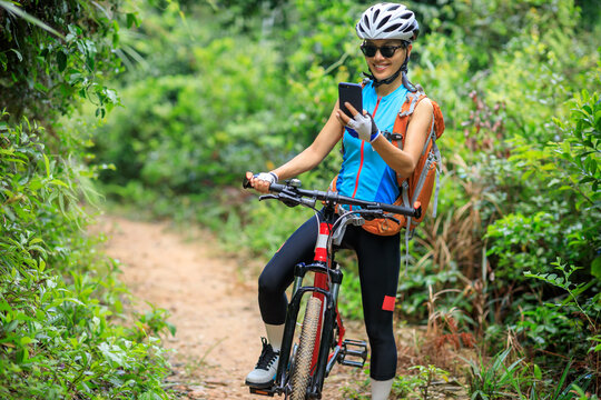 Woman cyclist use smartphone when riding mountain bike on forest trail