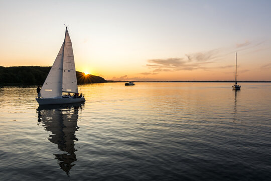 Sailing boats drifting back into the harbour during scenic sunset at the Baltic Sea