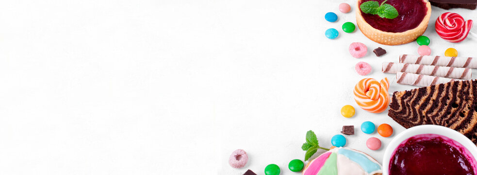 Web banner with sweets assortment on white table. Various confectionery products. Cakes, multicolored sweets, waffles and cookies. Copy space
