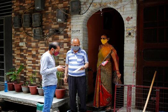 A volunteer from SEEDS, an NGO which normally specialise providing relief after floods and other natural disasters, registers a coronavirus disease (COVID-19) vaccination slot for a couple outside their house in New Delhi