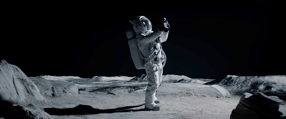 Obraz WIDE Male actor in astronaut suit making selfie on a Moon Lunar movie shooting set. Shot with 2x anamorphic lens - fototapety do salonu
