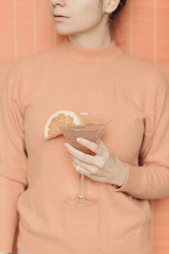 Crop woman with cocktail in studio