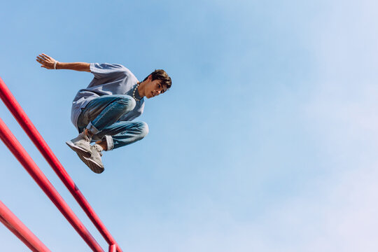 Young man jumping over railing in city