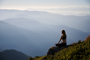 Young woman doing yoga in Lotus pose outdoor. Meditating female is relaxing on grass in mountains. Concept of workout.