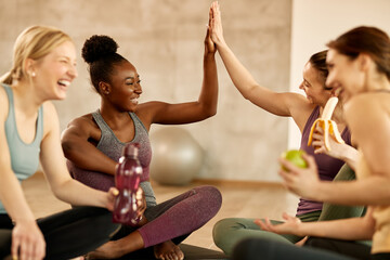 Happy athletic women giving high-five while relaxing after exercise class at health club.