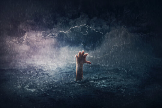 Arm drowning in the sea. Surreal and dramatic scene of person hand sinking in the ocean under a hurricane stormy weather. People need help in risk situations. Despair, depression and failure metaphor