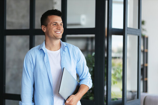 Headshot portrait of  caucasian successful freelancer or student with laptop in casual clothes, stands in office or college, smiling, business concept