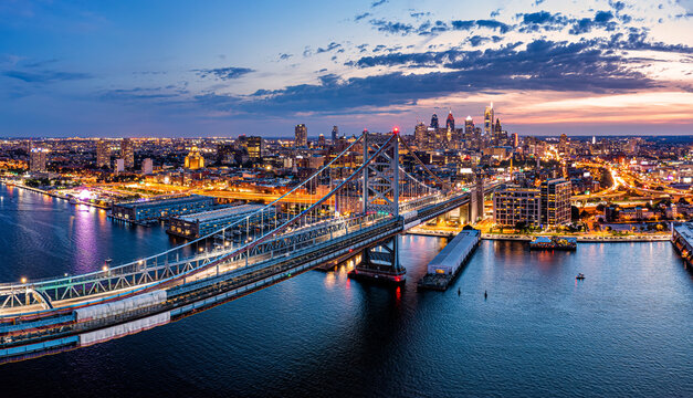 Aerial panorama with Ben Franklin Bridge and Philadelphia skyline in transition from sunset to dusk. Ben Franklin Bridge is a suspension bridge connecting Philadelphia and Camden, NJ.