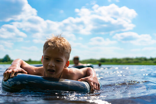 boy with a rubber ring floats in the summer. child swims in the lake in summer. summer children's entertainment