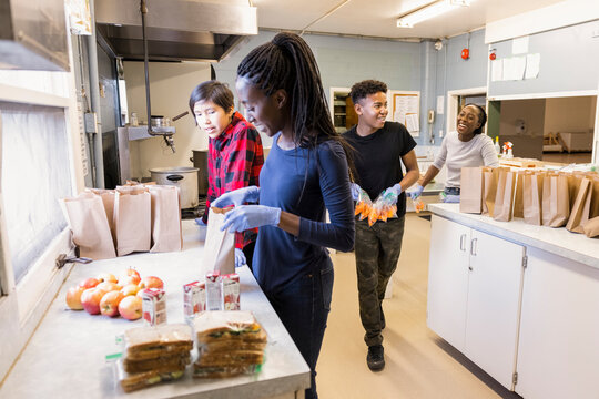 Volunteers packing sack lunches in community center kitchen