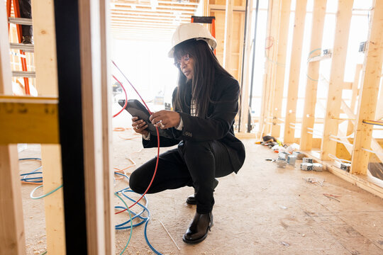 Female homebuilder with digital tablet inspecting construction wiring