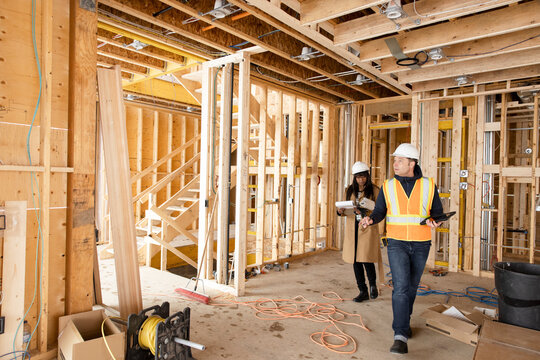Homebuilders inspecting framing at home construction site