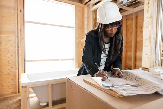Female architecture reviewing blueprints at home construction site