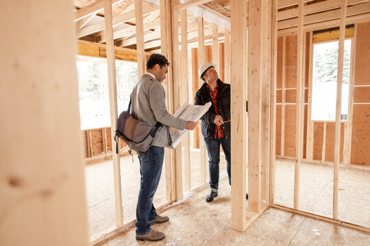 Male architect and homebuilder with blueprints at construction site