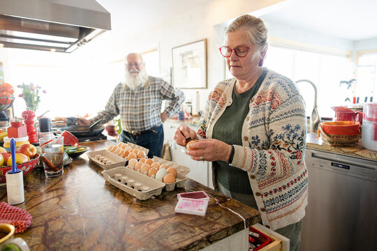 Woman stamping eggs in kitchen