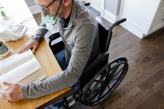 Senior man with oxygen mask in wheelchair reading book at table