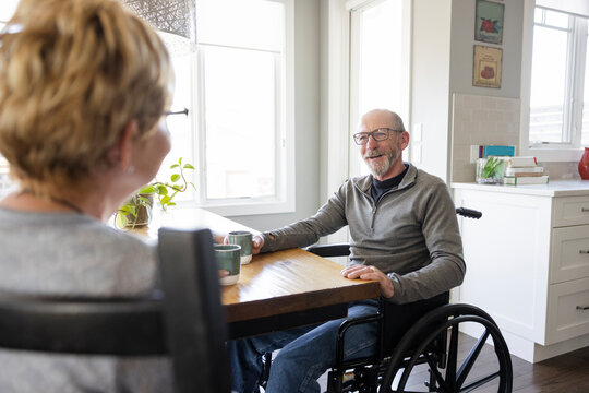 Happy senior husband in wheelchair talking to wife at dining table