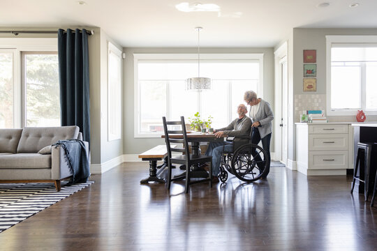 Senior man in wheelchair with wife at dining table