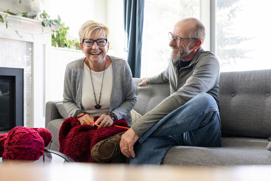 POV portrait happy senior couple knitting and video chatting on sofa