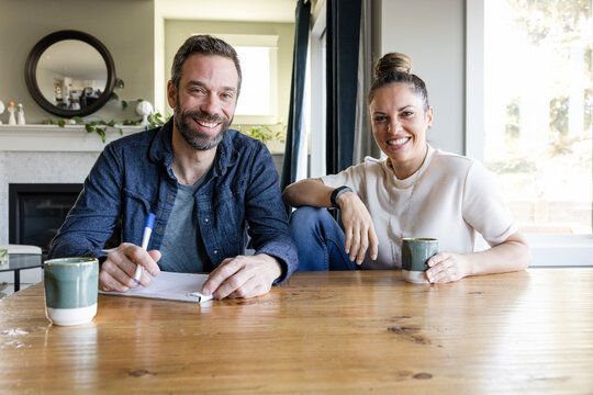 Portrait happy couple with coffee making a list at dining table