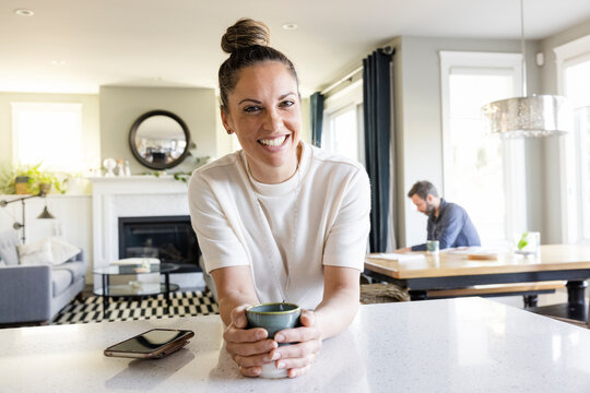 Portrait happy woman drinking coffee at kitchen counter
