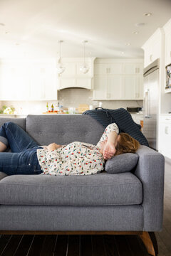 Tired woman resting on living room sofa