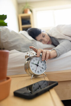 Tired woman in bed snoozing alarm clock in morning bedroom