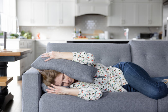 Woman with migraine headache laying on sofa with head between cushions