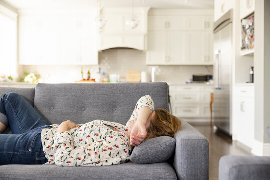 Woman with headache resting on living room sofa