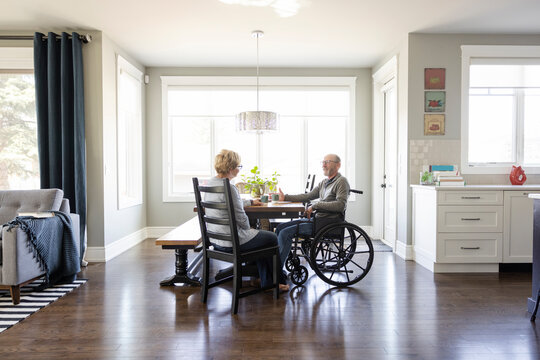 Senior wife talking with husband in wheelchair at dining table
