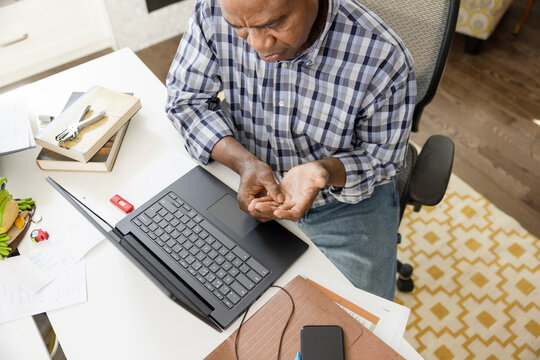 Man explaining arthritis in telemedicine video chat from home laptop