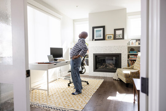 Mature man working from home stretching back in home office