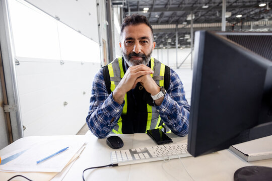 Construction supervisor working on computer on desk in warehouse