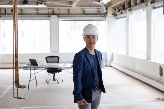 Portrait of architect in hard hat working on office remodel