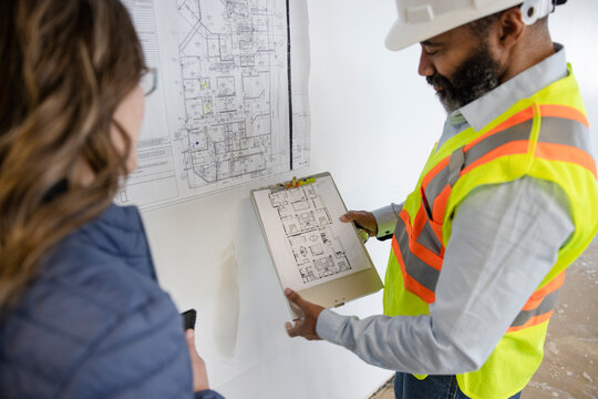 Architect and construction foreman looking at building plans