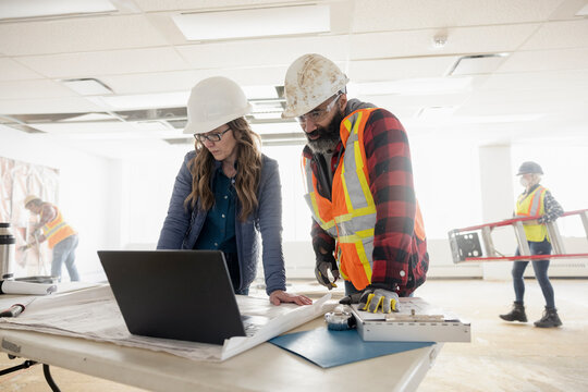 Site manager and construction foreman looking at laptop