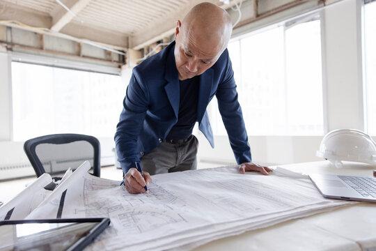 Man working on plan of building interior
