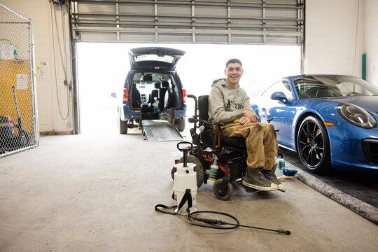 Portrait confident disabled male worker detailing sports car