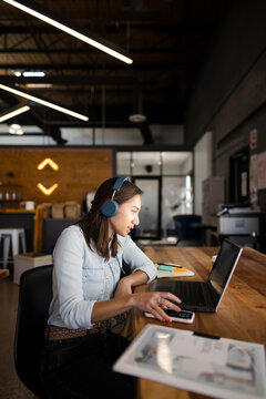 Creative young businesswoman with headphones working at laptop