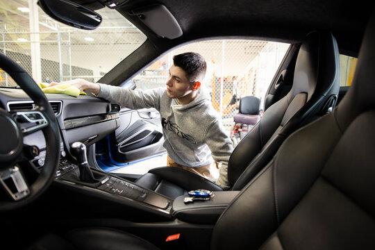 Male worker detailing inside of sports car
