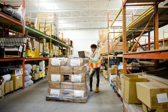 Teenage boy working at laptop on stack of boxes in warehouse