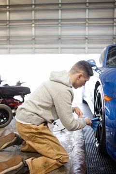Male worker detailing wheels on sports car in auto body shop