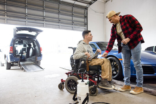 Disabled male worker talking with colleague in auto body shop
