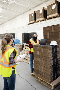 Warehouse workers in face masks talking and social distancing