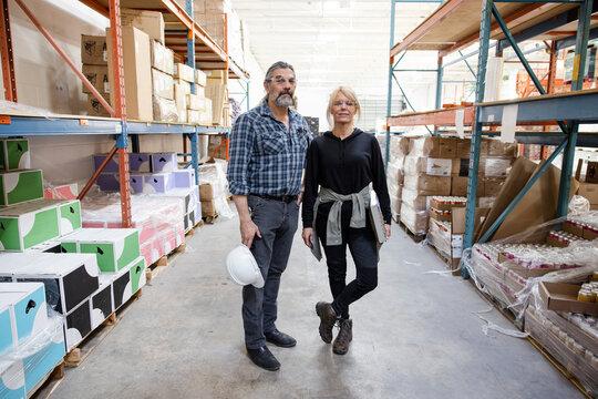Portrait confident warehouse managers in aisle
