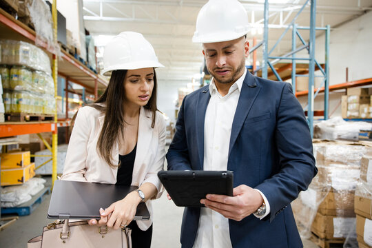 Business people in hard hats using digital tablet in warehouse
