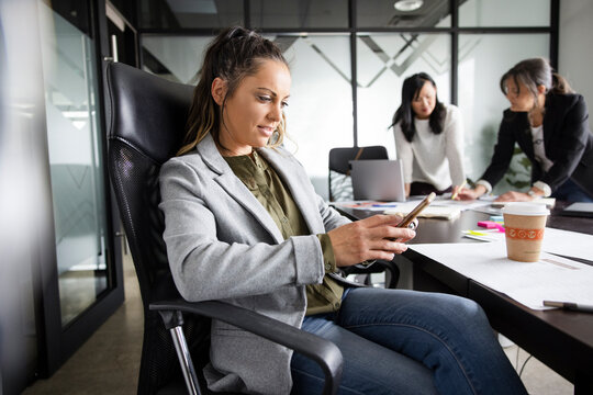 Businesswoman using smart phone in conference room meeting