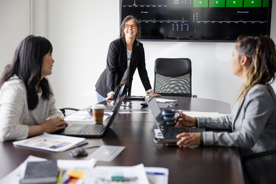Happy businesswoman leading conference room meeting